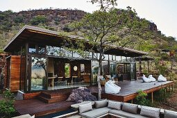 Modern safari lodge with glass façade and spacious wooden terrace in wild landscape