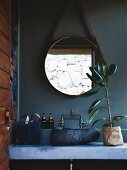 Concrete washstand with stone basin below round mirror on petrol-blue wall