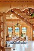 View under staircase of modern chairs around table in living area of solid-wood house