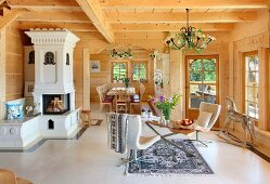 Open-plan interior of wooden house with fireplace