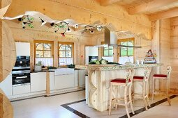 Breakfast bar and carved wooden bar stools with painted sections in open-plan modern kitchen in solid wooden house
