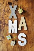 Rustic wooden letters spelling XMAS and tiny gift-box ornaments