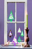 Christmas trees hand-crafted from paper in old window frame