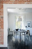 View of dining set through doorway in brick wall with white frame