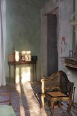 Antique chair with gilt Rococo-style wooden frame and delicate washstand in rustic Mediterranean interior