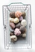 Balls of pastel wool in shopping basket