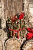 Rote Kerzen und Beeren in mit Zweigen umwickeltem Blumentopf