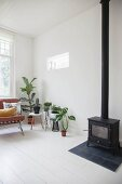 Houseplants and log burner in Scandinavian living room
