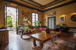 Ghost chairs at solid wooden table in open-plan, eclectic Mediterranean interior with open double doors leading to courtyard