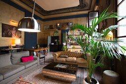 Loungebereich mit Sofas und Zimmerpalme in eklektizistischem Wohnzimmer mit historischem Flair