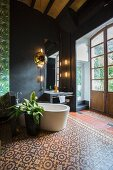 Free-standing bathtub and foliage plant on ornamental tiled floor