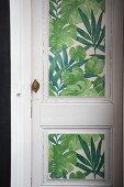 Weiße Vintage-Zimmertür mit grüner floral gemusterter Tapete beklebt
