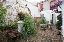 Plants and outdoor furniture on gravel in courtyard of old, two storey house