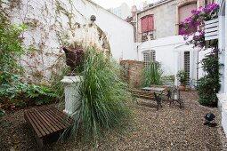 Begrünter Innenhof eines mehrstöckigen, alten Wohnhauses, mit Outdoormöbeln auf Kiesfläche