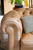 Arm of beige, button-tufted leather sofa with black and white patterned scatter cushion