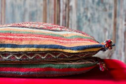 Bunt gestreifte Kissen mit folkloristischem Muster