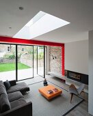 Grey couch, designer armchair and low orange coffee table in modern interior with skylight