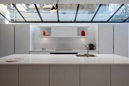 weiße Designerküche mit Küchentheke unter Glasdach