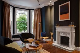 Black-painted room with bay window, retro seating and open fireplace