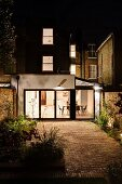 Courtyard with paved area at night and view into modern extension with illuminated interior