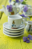 Crockery with Peter Rabbit motif and violas on yellow-painted wooden table