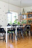 Black designer chairs around white table below pendant lamps in Scandinavian-style dining room