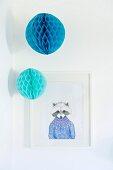 Zwei aufgehängte Papierpompons in Blautönen vor weiß gerahmter Zeichnung mit verfremdetem Waschbärmotiv