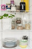 Storage jars and crockery on open kitchen shelves
