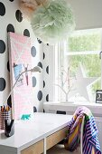 Desk against polka-dot wall and below large pompoms