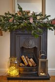 Fairy lights in large glass jar and lantern on hearth of cast iron fireplace with festive arrangement on mantelpiece