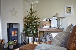 Decorated Christmas tree between wood-burning stove and gifts on console table in rustic living room