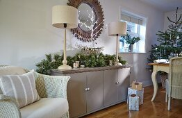 White-painted wicker armchair next to festive arrangement and table lamps on sideboard with Christmas tree in background