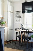 Black bistro chairs around wooden table in dining area in kitchen below window and next to white fitted fridge-freezer