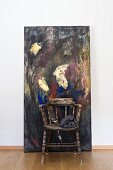 Vintage wooden armchair in front of modern painting
