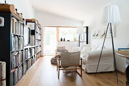 Designer standard lamp next to white loose-covered sofa and bookcase with TV in centre in living room