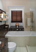 Dark marble washstand counter, white bathtub and glass shower screen in bathroom