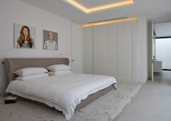 Grey double bed with upholstered headboard and white fitted wardrobes in modern bedroom