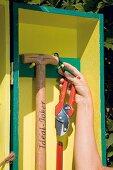Secateurs and spade hanging in DIY garden cupboard