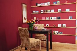 Dark wooden table and two rattan chairs in front of narrow DIY shelves on claret-red wall
