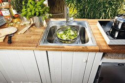 White-painted DIY kitchen base units with sink fitted in worksurface in outdoor kitchen