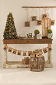 Small Christmas tree on rustic wooden table and Advent calender made from paper bags