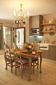Dining table set for Easter below elegant chandelier in fitted kitchen