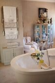 Free-standing bathtub with toiletries on bath caddy and towel rack above cabinet in background