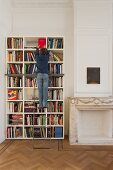 Boy climbing library ladder in front of bookcase next to fireplace with marble surround