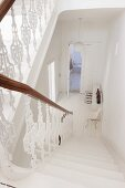 White balustrade in stairwell leading down into white hallway of period apartment