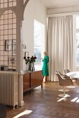 Woman in retro dining room with lead-glazed partition