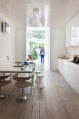 Woman walking into kitchen with high-gloss surfaces, retro chairs and wooden floor