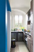 Narrow kitchen with blue wall