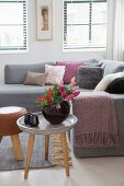 Vase of flowers on three-legged table in front of sofa with many scatter cushions