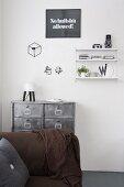 Braunes Sofa vor Metall- Schubladenschrank an weißer Wand mit String-Regal und Wanddeko